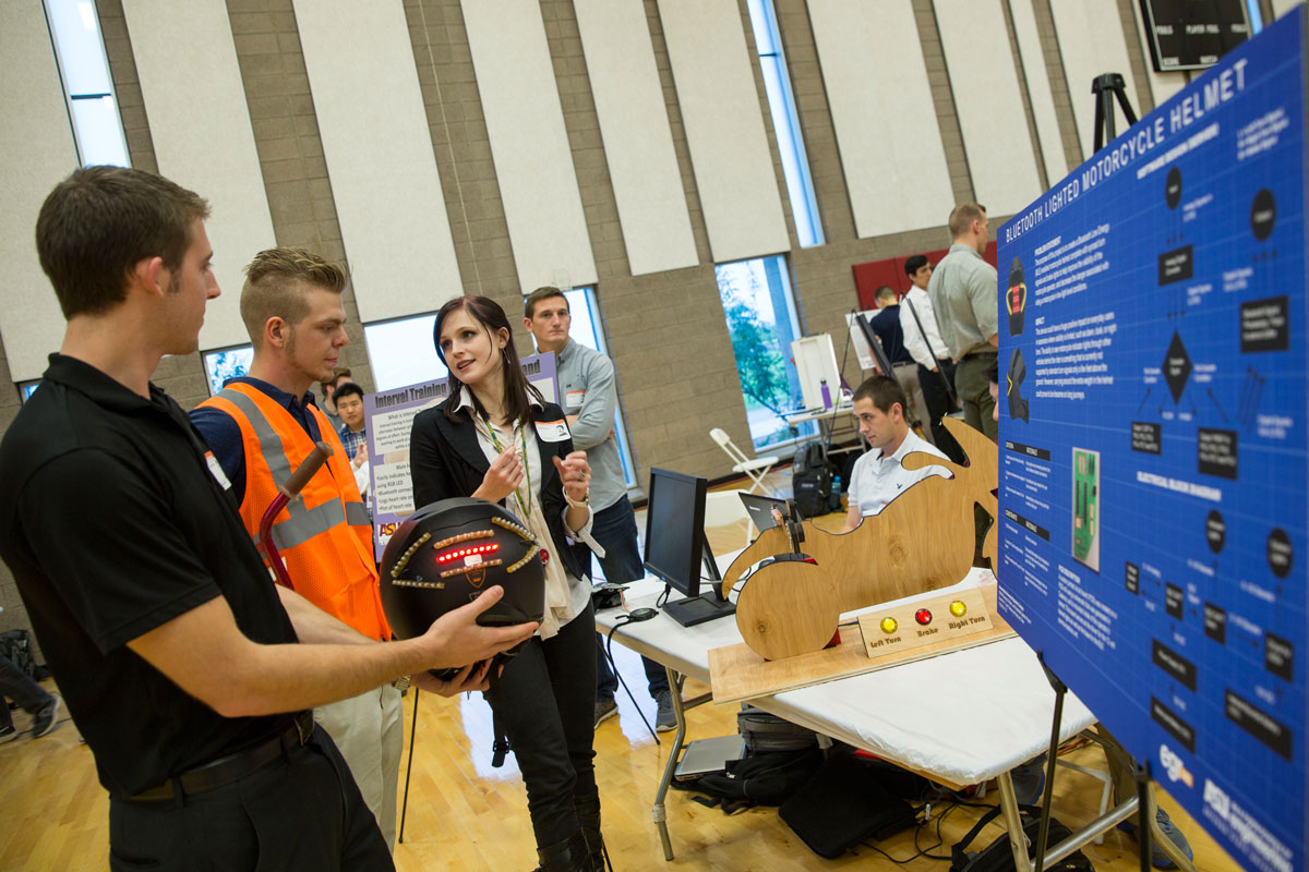 Students show a Bluetooth lighted motorcycle helmet at the Fall 2015 Innovation Showcase.