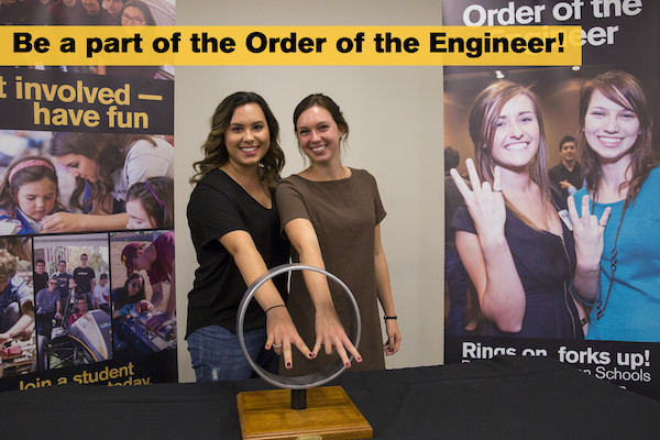 "This photo shows two female students with their hands through a large ring with overset text ""Be a part of the Order of the Engineer"""