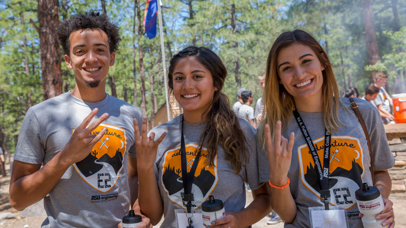 Three students pose at E2 camp.