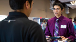 A student talks with a recruiter at a career fair