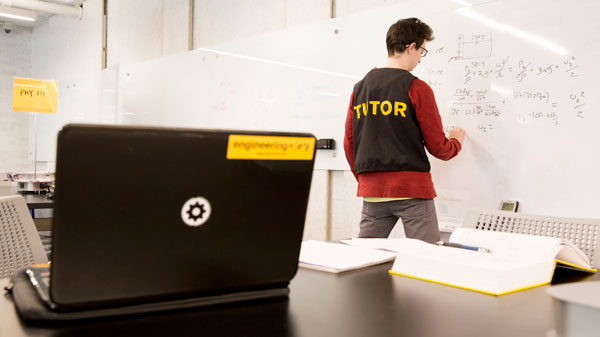 A tutor works on a white board at the tutoring center.