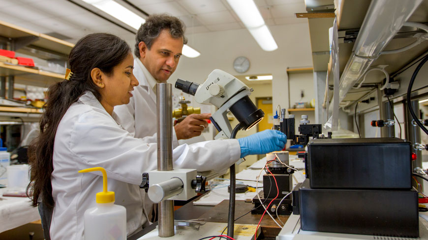 A student and faculty member work in the lab.