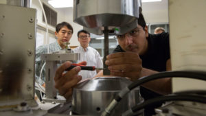 A student works in Yongming Liu's lab whole two others look on.