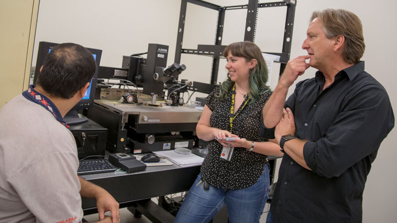 Two graduate students work with Professor Michael Kozicki in his lab.