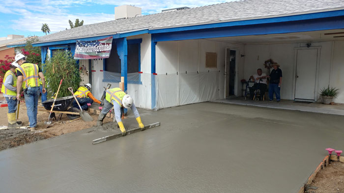 A student smooths out the poured concrete.