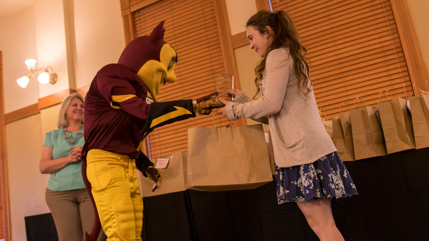Sparky hands an award to a student.