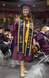 A woman with a veteran stole poses at Convocation.