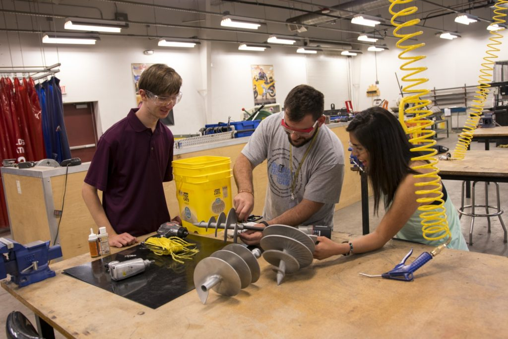 Three students work on a project.