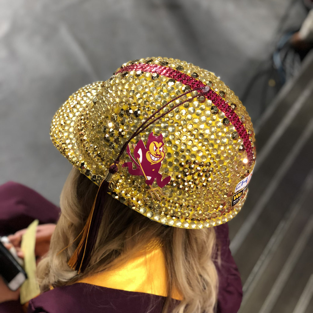 A hard hat bedazzled with gold rhinestones.