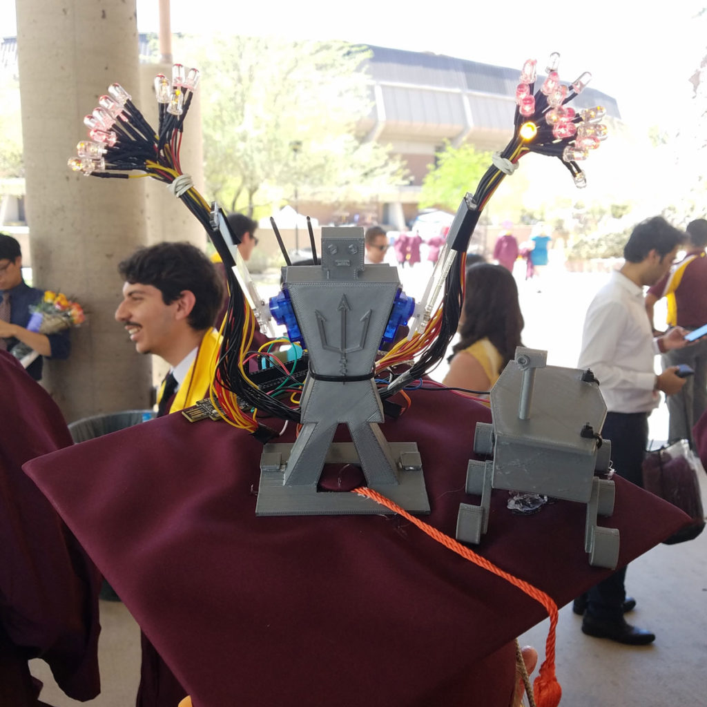 Photo of a grad cap with a 3D printed robot and LED lights.