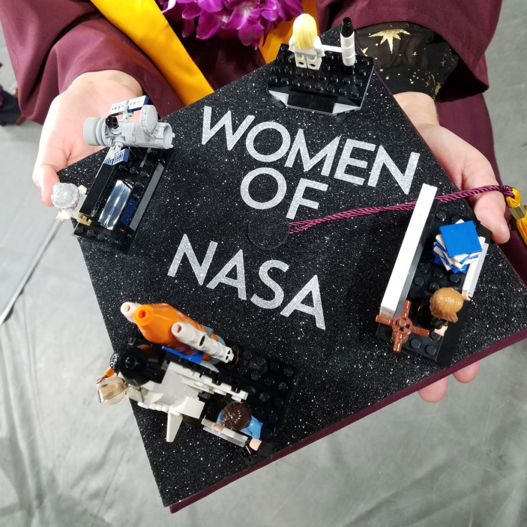 "Photo of a grad cap that says ""women of NASA"" with LEGO models of NASA projects led by women."