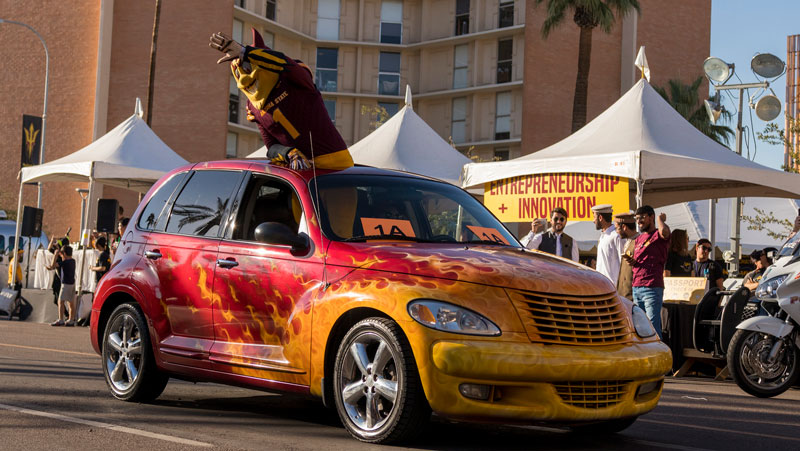 Sparky waves from a car decorated with flames.