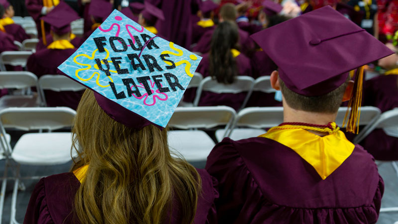 """Two students at graduation wearing their grad cap and gown. One grad cap has the words """"Four years later"""" decorated on it."""
