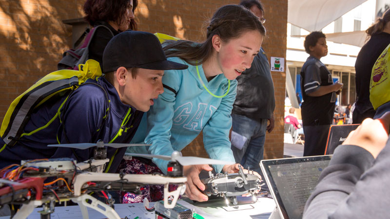 Two young visitors play with a drone controller.
