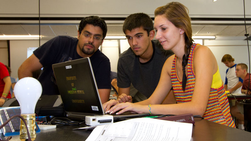 Three students work on a laptop.