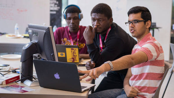 Three students work together on a laptop.