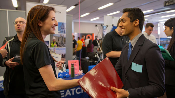 A recruiter and student shake hands at Career Fair.