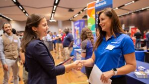 A student shakes hands with a recruiter at a career fair.