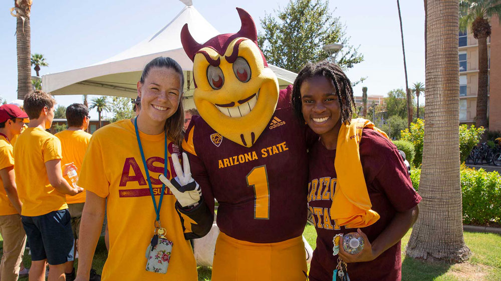 Two students pose with Sparky